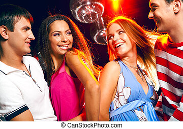 Clubbers - Two excited couples looking at each other with...