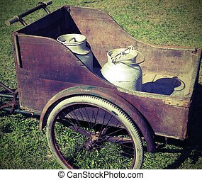 two old milk cans transported with an old wagon and vintage...