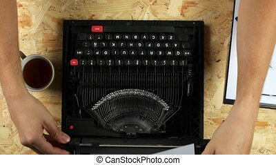 Sings typing the text of his verse on a typewriter. View...