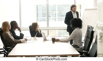 Businessman giving presentation to multi-ethnic clients...