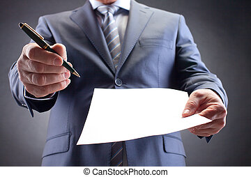 Agreement - Close-up of businessman holding paper and pen...