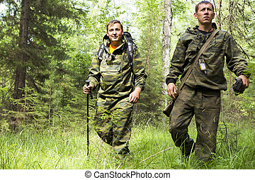 Foresters patrolling the forest. - Adult men in the form of...
