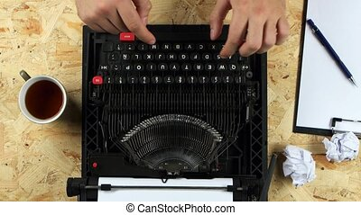 Guy type the text of the book on a typewriter. View from...