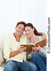 Portrait of a happy couple looking a photo album in the...