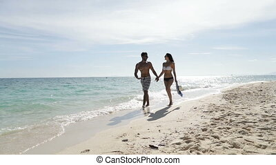Couple Walking On Beach Holding Hands Talk, Man And Woman...