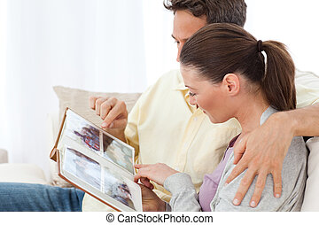 Lovely couple looking at pictures on a photo album on the...