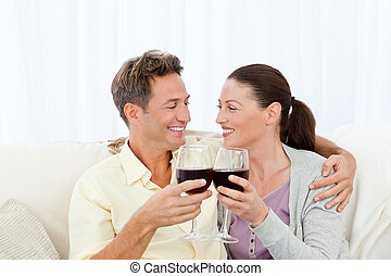 Passionate couple drinking red wine while relaxing on the...