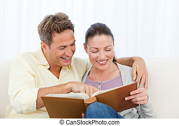 Couple smiling while looking at pictures on a photo album at...