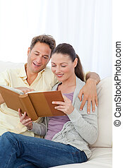 Cute couple looking at a photo album on the sofa at home