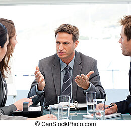 Charismatic manager talking to his team at a meeting