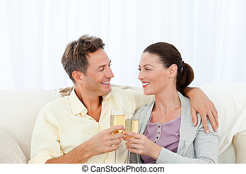 Cute couple drinking champagne while relaxing on the sofa