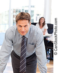 Confident man posing in front of his colleague during a...