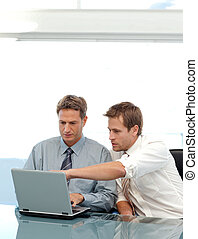 Businessmen working together on a laptop at a table at work