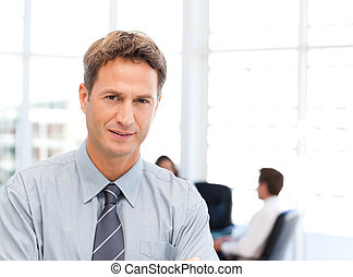 Severe businessman standing in front of his team while...