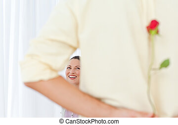 Rear view of a man hiding a rose for his girlfriend in the...
