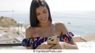 Charming woman using phone on resort - Young happy model in...