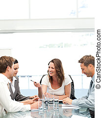 Cheerful manager talking to her team during a meeting in the...