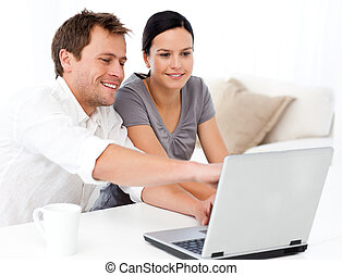Cute man showing something on the laptop screen to his...