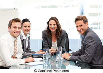 Serious businesswoman with her team at a table during a...