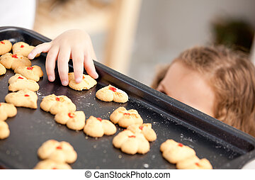 Little girl taking a cookie