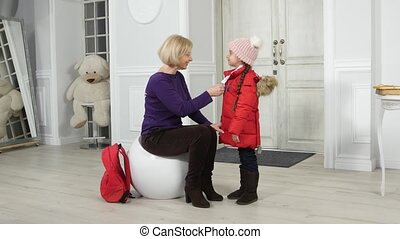 Mom wears a jacket and hat to his little daughter in the...