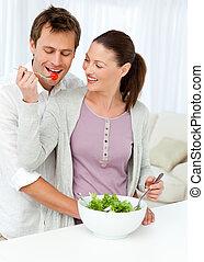 Pretty woman giving a tomato to his boyfriend