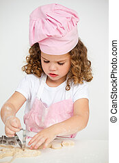 Cute little girl making biscuit at a table in the kitchen