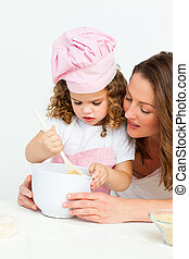 Cute girl  preparing a cake with her mother