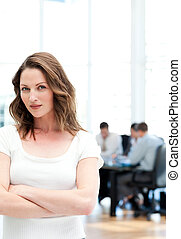 Confident woman standing at a meeting while her team working...