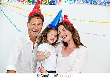 Portrait of cute little girl with her parents during a birthday