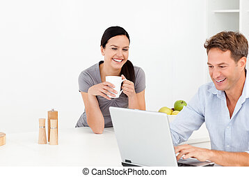Cheerful couple looking at something on internet while drinking coffee in the kitchen