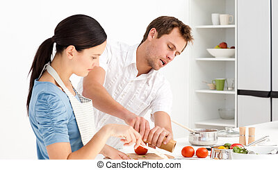 Man putting salt and pepper while his girlfriend stiring the...