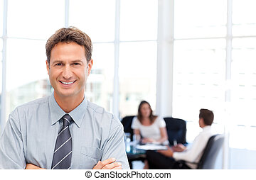 Proud businessman posing in front of his team while working...