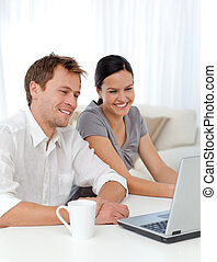 Lovely couple laughing while looking at a video on the...