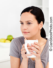Quiet woman drinking her coffee in the kitchen