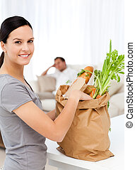 Happy woman with bags in the kitchen after shopping