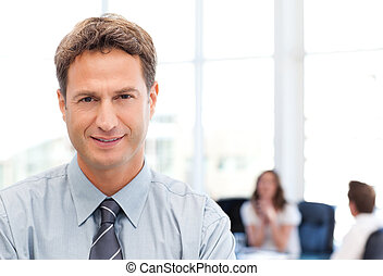 Relaxed businessman posing in front of his team while...