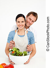 Happy man mixing a salad with his girlfriend in the kitchen...