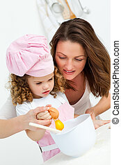 Mother and daughter breaking eggs while cooking together in...
