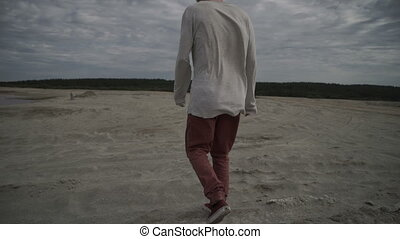 Handsome man walking on beach - Handsome young man walking...