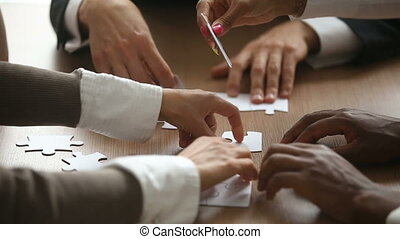 Business people trying to connect jigsaw puzzle, teamwork...