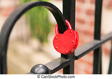 Red heart lock hanging on black cage - Close focus on empty...