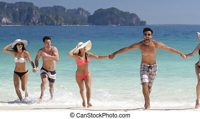 People Running From Water Holding Hands On Beautiful Beach,...