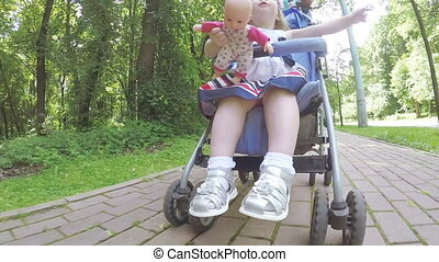 Mom and daughter in a stroller - In the baby carriage a...