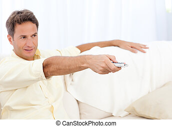 Relaxed man changing channel while watching tv on the sofa