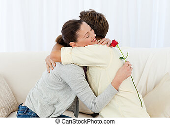 Lovely woman hugging his boyfriend after receiving a flower...