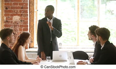 African american boss discussing project at meeting with...