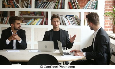 Successful businessman negotiating with business partners at...