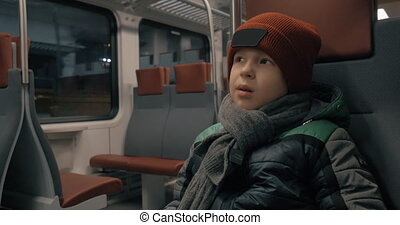 Boy traveling by suburban train - Boy sitting quietly in...