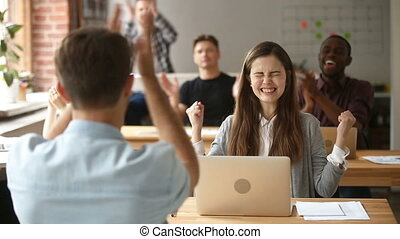 Multi-ethnic team cheering female coworker with applause in...
